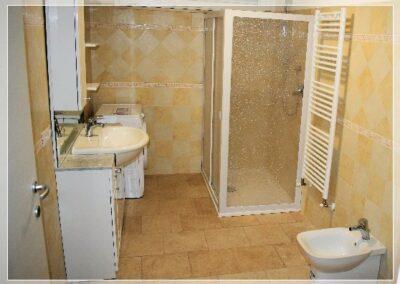 Bagno con doccia e lavatrice per bucato